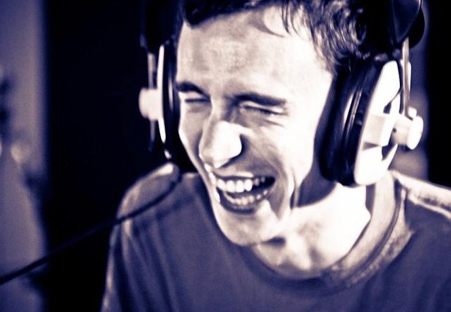 Jeremy wearing headphones and laughing in the recording studio